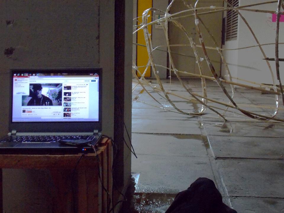 """Imagem de notebook com tela do YouTube. Ao fundo, a estrutura do """"baseado alegórico""""."""