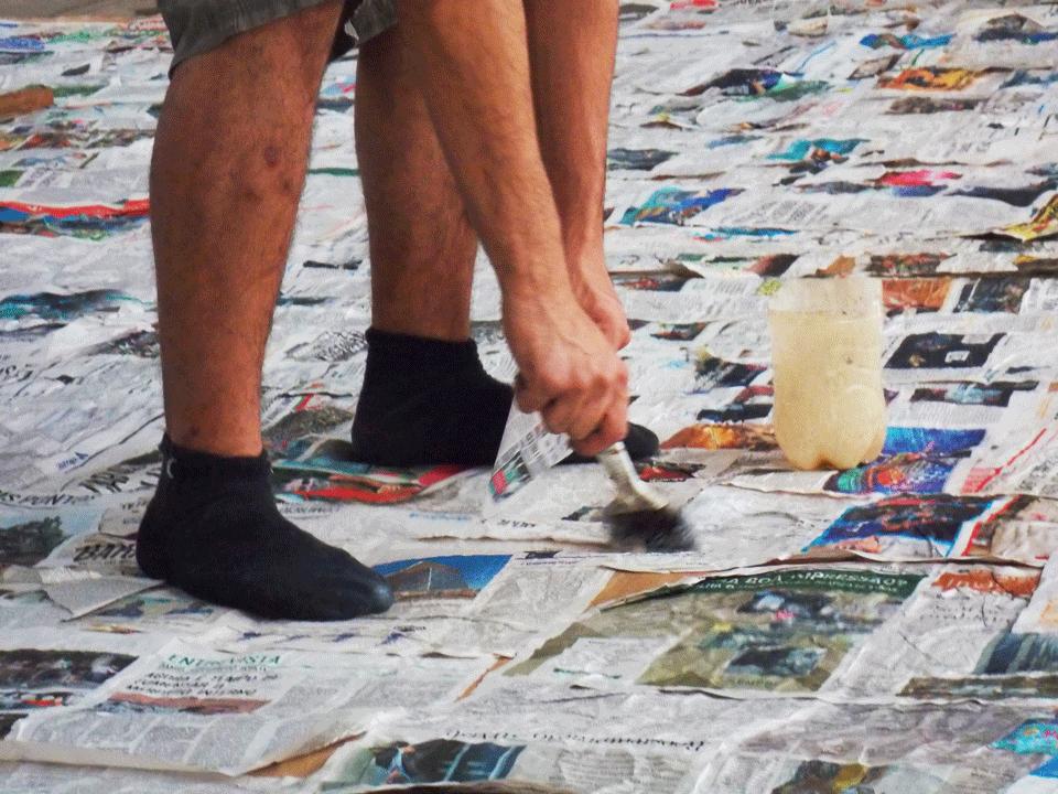 Homem passa cola com um pincel sobre jornais. Na imagem só é possível ver os pés e as mãos dele,.