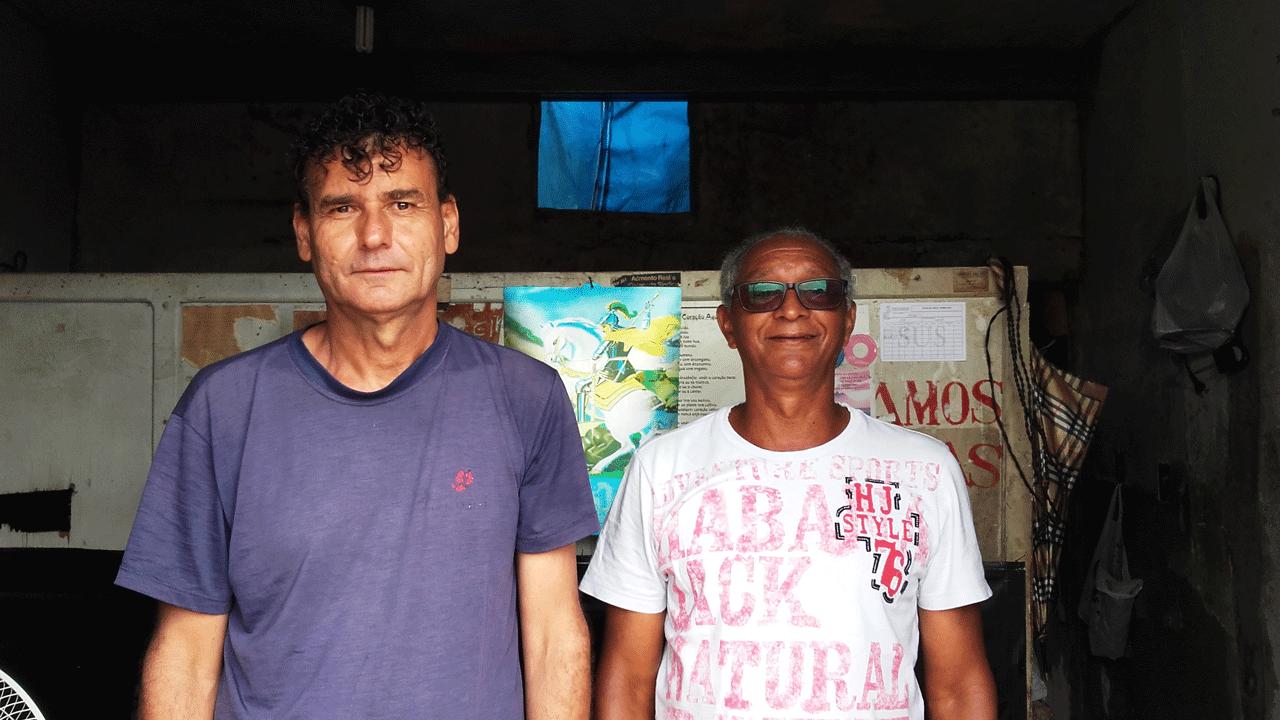 Foto. Walmir Afonso, um homem branco de cabelos escuros encaracolados, está de pé ao lado de Walmir Afonso, um homem negro mais baixo e com cabelos brancos,, que usa óculos de sol.