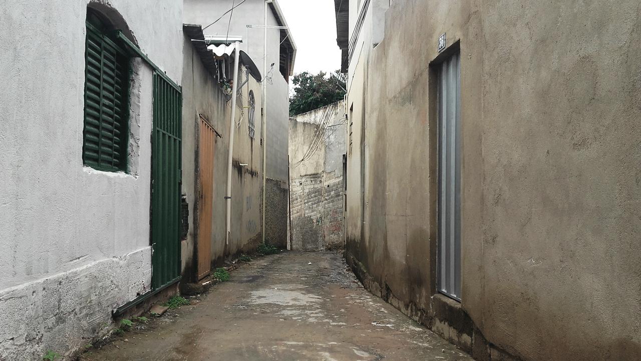 Foto do Beco Tucano. As casas não tem muro, as portas dão direto para a rua, que é estreita. O cinza é a cor predominante.