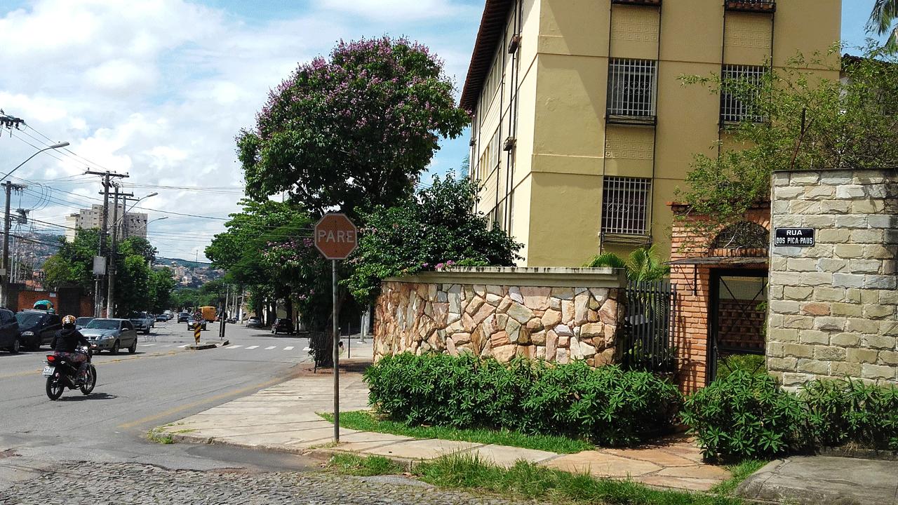 Foto de uma casa na esquina do Vila Clóris. A casa é um pequeno prédio amarelo, com um muro baixo de pedras enfeitado com arbustos.