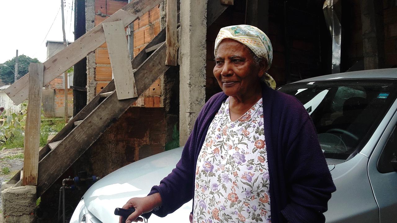 Foto de Maria Aparecida, mulher negra com um lenço sobre os cabelos. Ela está diante de um carro e segura uma bengala.