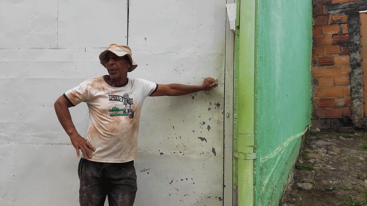 Foto de Anselmo Paulo, homem negro que usa um chapéu claro, escorado a um portão.